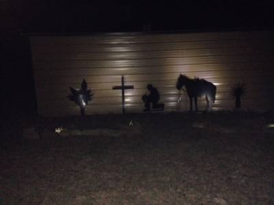 Barn scene of praying cowboy with lighting installed